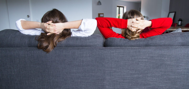 Widok z tyłu współlokatorów relaksujących się na kanapie